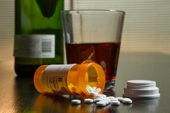 Om afhængighed - En tom flaske rødvin og et glas med piller